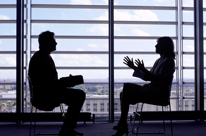 Two people talking in silhouettes